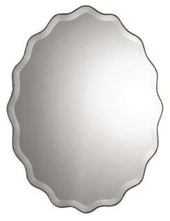 This ovalshaped wall mirror features a scalloped edge finished in